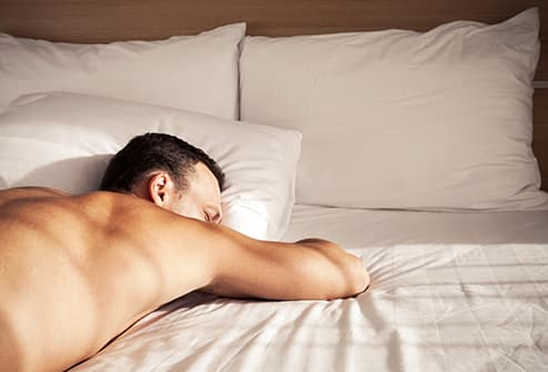 woman sleeping with arms under pillow