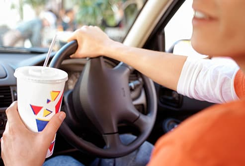 man holding fast food soft drink in car