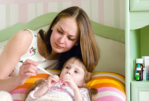 mother checking childs temperature