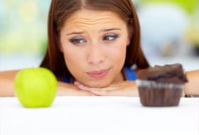 woman looking at apple ans cupcake