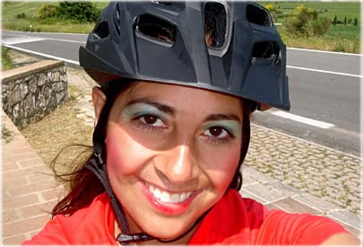 Heavily made up woman wearing helmet in bright sun