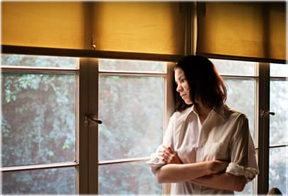 Depressed woman with acne staring out window