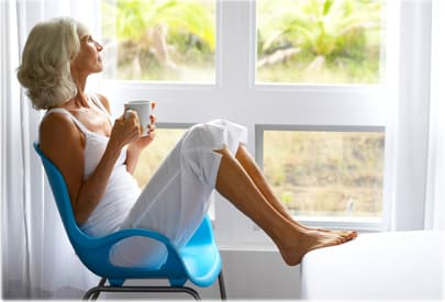 Woman drinking coffee in bedroom, looking out