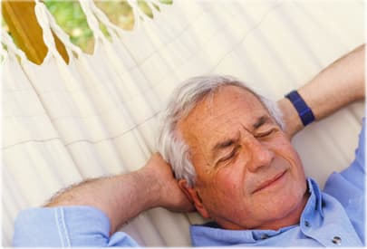 Senior man lying on hammock, eyes closed