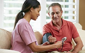 Woman checking mans blood pressure thumb