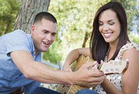 man and woman playing guitar in park