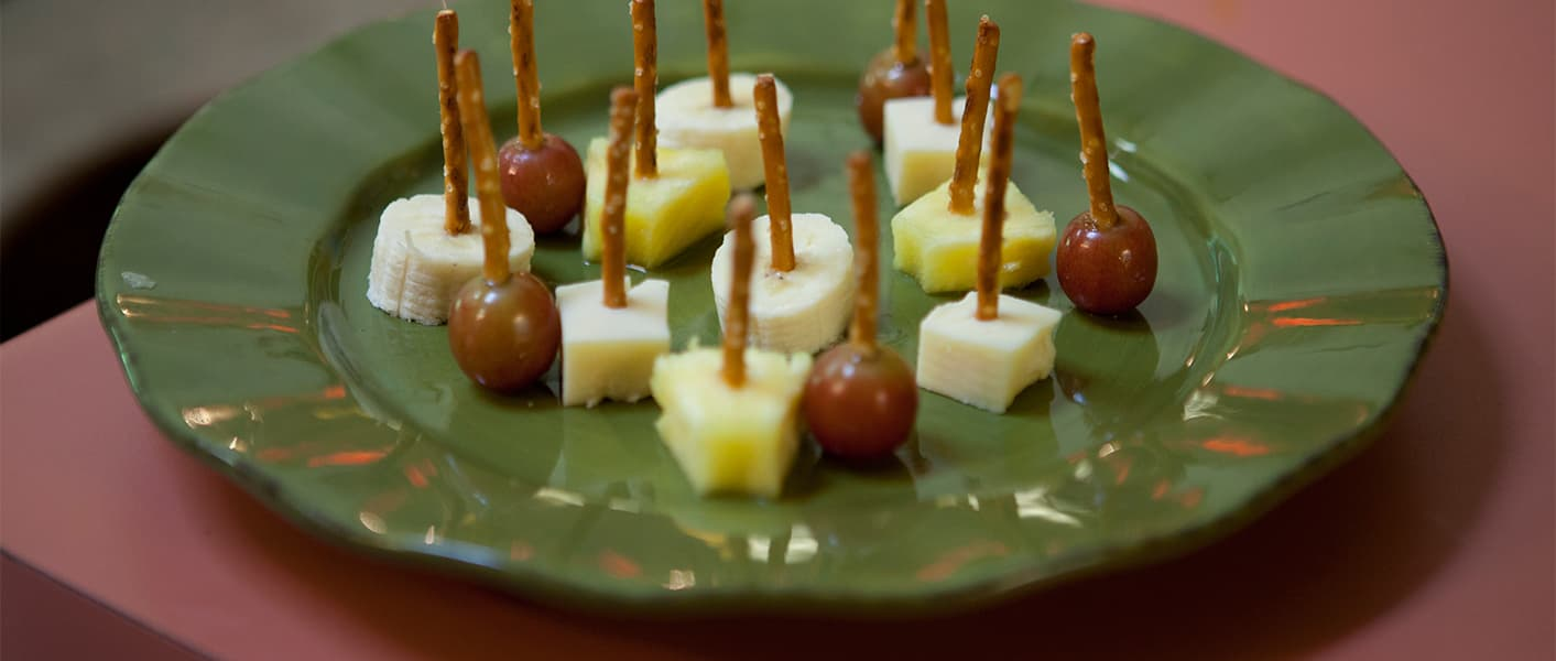 pieces of fruit with pretzel toothpicks