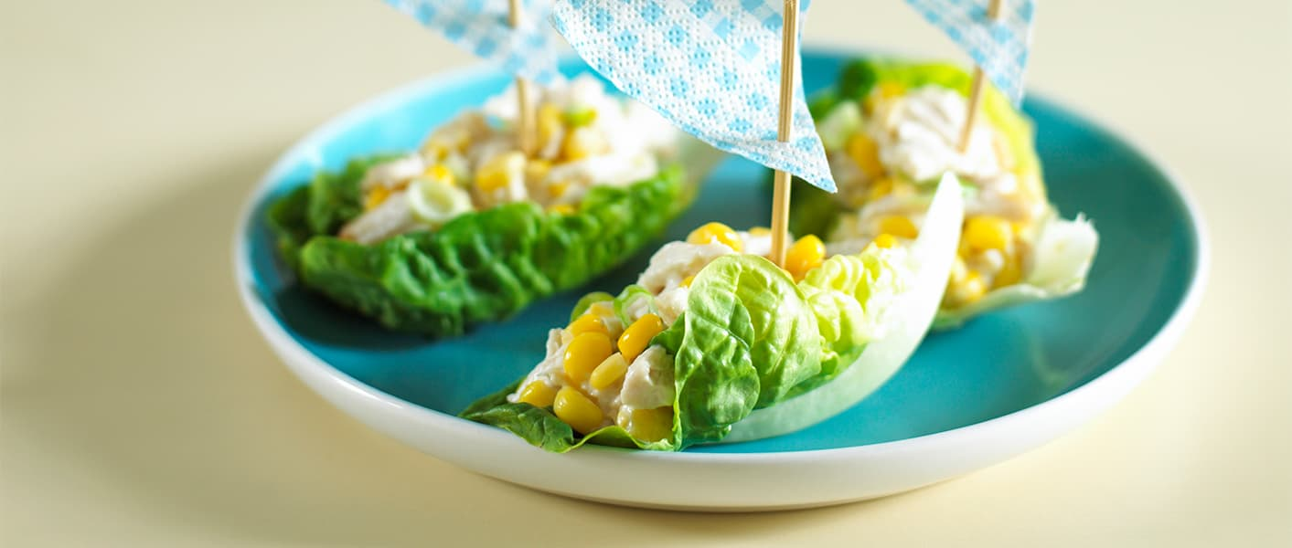 sailboats made out of lettuce, chicken, and corn