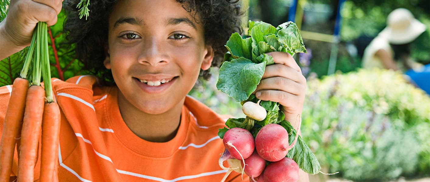 boy holding carrots and radishes