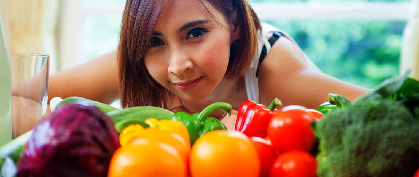 girl and table of fresh vegetables