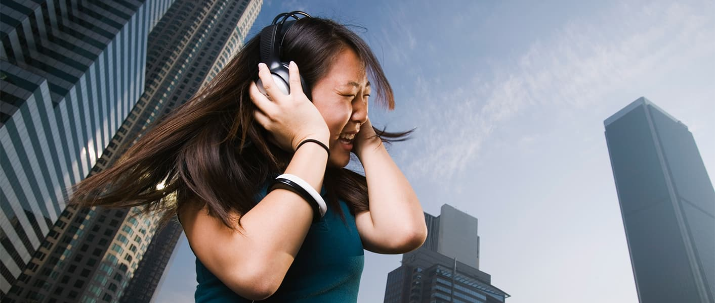 girl listening to headphones in city