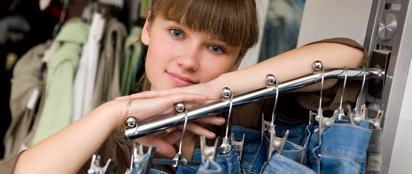 girl leaning on rack of jeans