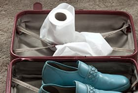 suitcase with shoes and colostomy bag