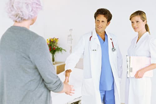 photo of hospital staff meeting with patient