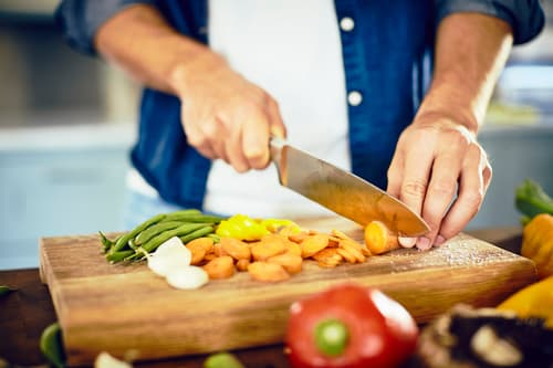 photo of man cutting vegetables