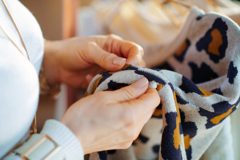 photo of woman checking sweater for damage