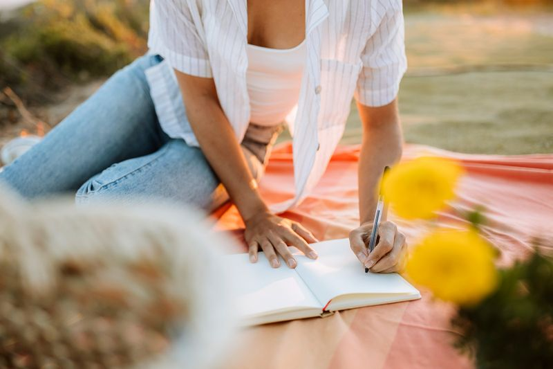 photo of woman writing in journal