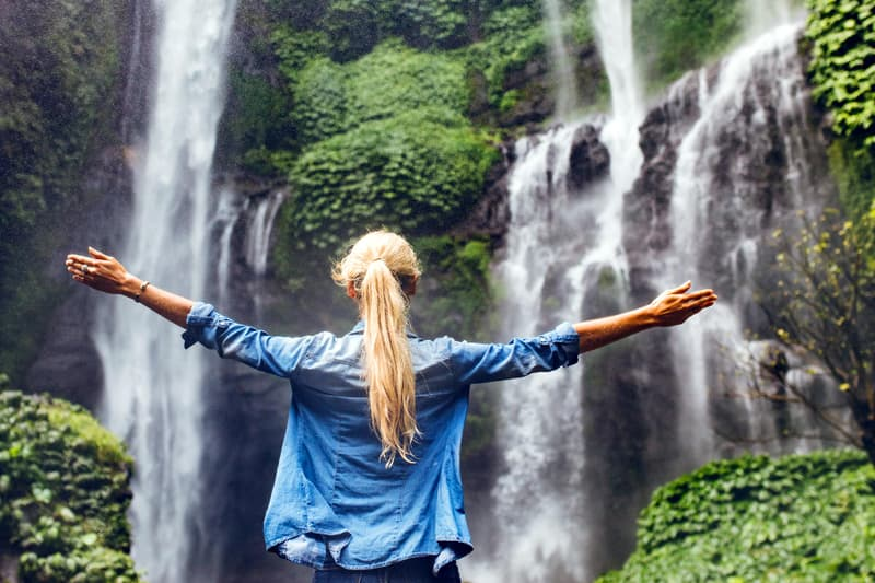 photo of woman standing by waterfall