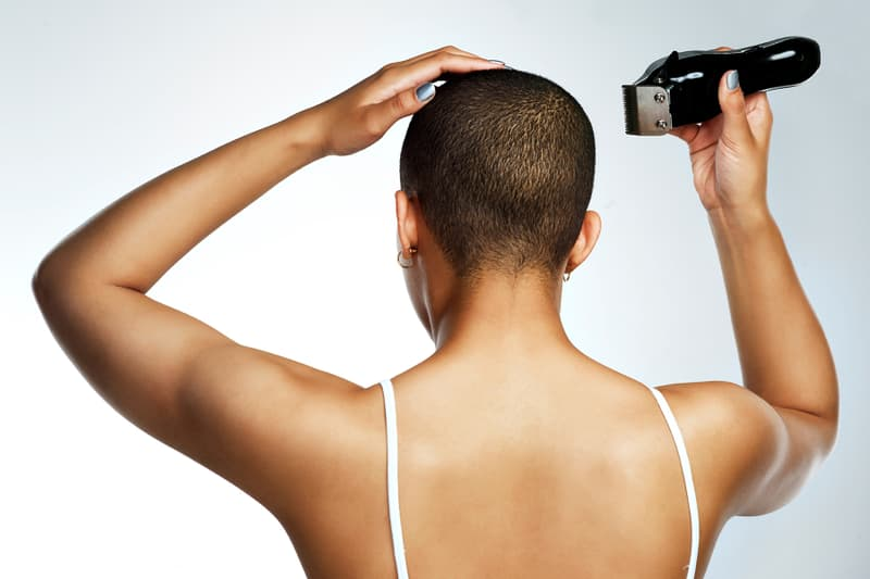 photo of young woman shaving her head
