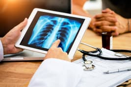photo of doctor explaining lung x-ray to patient