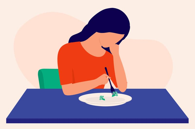 photo of young depressed woman picking at food