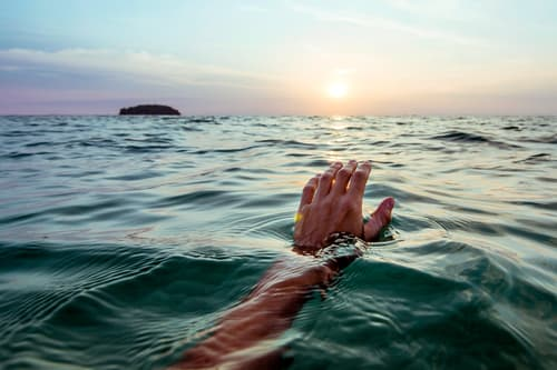 photo of swimmer hand rising from ocean at sunset