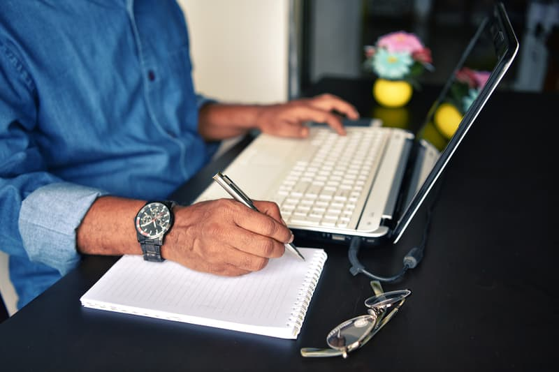 photo of hands of man working on laptop computer