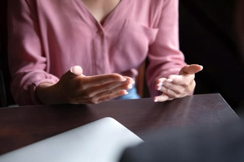 photo of woman gestering with hands during talk