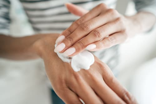 woman putting lotion on her hands