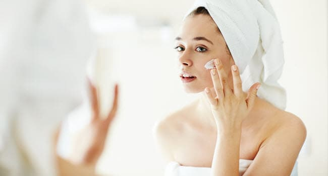 woman applying lotion on face