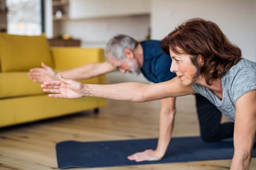older couple doing yoga at home