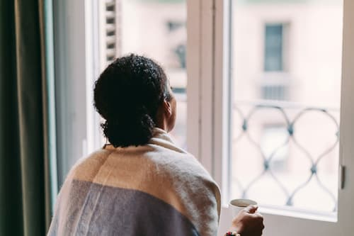 photo of woman looking out window