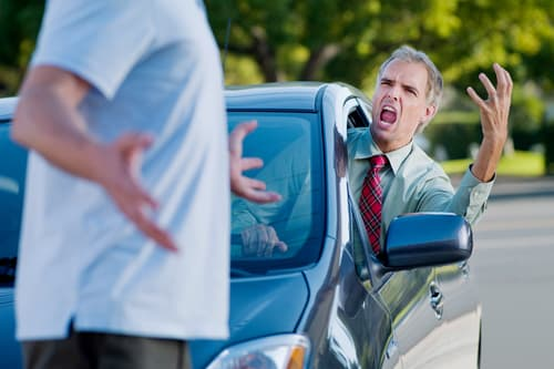 photo of man in car yelling at pedestrian
