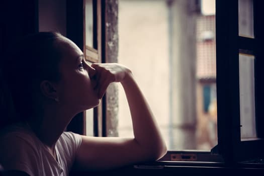 woman looking out the window with sadness