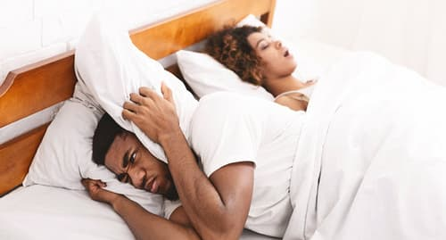 irritated man sleeping next to woman snoring