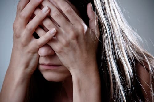 photo of depressed woman with head in hands