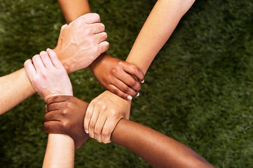 photo of five mixed hands clasped in unity