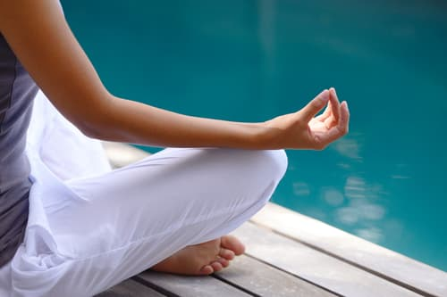 photo of woman meditating by the pool