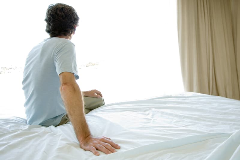 photo of man sitting on bed
