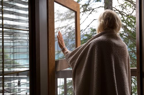 photo of woman looking out door
