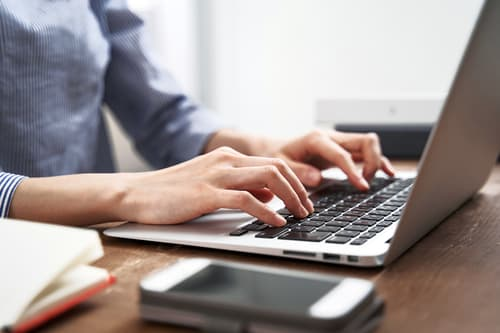 photo of woman working on laptop at home