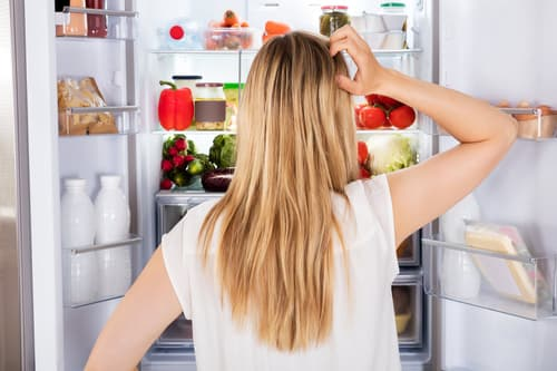 photo of woman looking in refrigerator