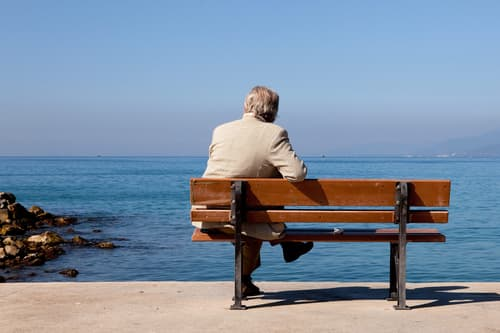 photo of man sitting alone on bench by water