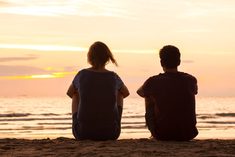 photo of friends sitting together on beach
