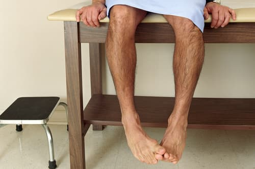 photo of male patient sitting on examining table