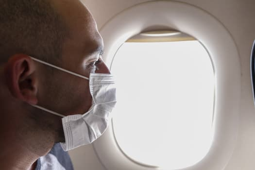 man in mask on airplane
