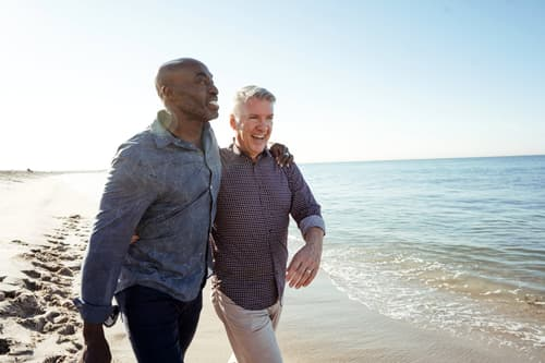 male couple walking on beach