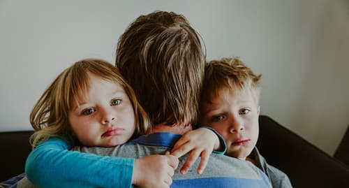 father hugging sad children