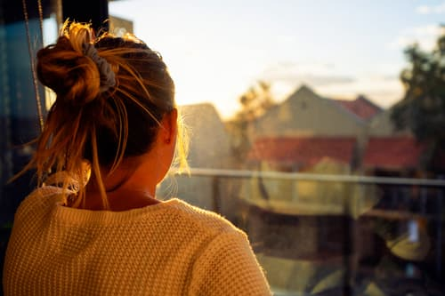 photo of woman looking through window at sunse