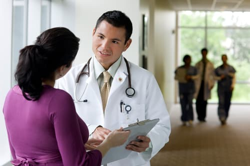 photo of doctor talking with co-worker